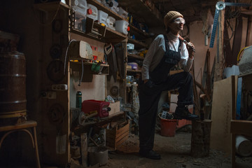 Portrait of smiling young builder girl standing in old workshop room, wearing construction glasses.