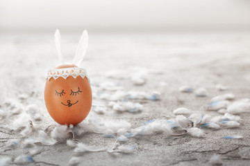 Decorated Easter egg and cute bunny's ears on gray table with white feathers