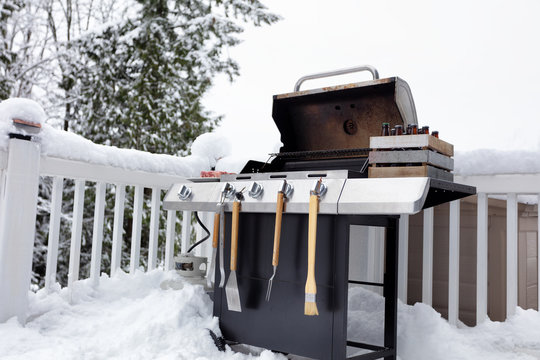 Barbecue cooker with bottled beer and beef meat ready for use in winter time