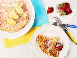 Shrove Pancake Tuesday pancakes with lemons and strawberries with lens flare.
