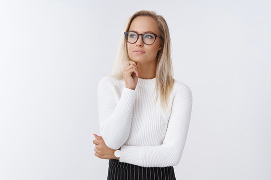 Woman decides how improve sales and income as posing in glasses and office outfit over white background looking away with thoughtful gaze touching chin, thinking, counting in mind