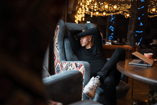 Fashionable young man in stylish black clothes in stylish sneakers sits on a soft vintage chair near the window in an expensive beautiful restaurant. Nice guy made a lunch break.