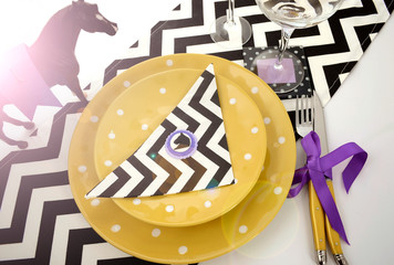 Horse racing carnival event luncheon table place setting in purple, yellow theme, and black and white chevron strip table runner, with lens flare.