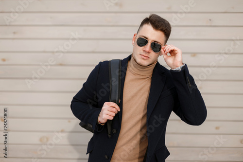 ccb58d59de3 Attractive young hipster man in stylish glasses in a fashionable jacket in  a vintage knitted sweater with a stylish hairstyle with a backpack on the  ...