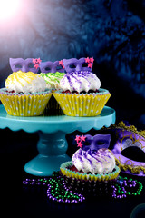 Mardi Gras cupcakes with small mask toppers made from confectionery sugar, against a vivid blue background.