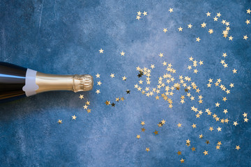 Champagne bottle and confetti stars on ultra violet background.  Christmas, birthday, carnival concept.