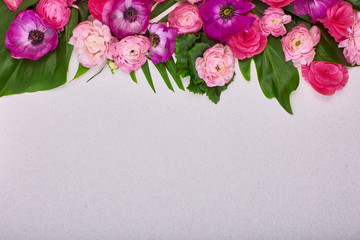 Beautiful floral background and green leaves, texture, wallpaper. Flat-lay of pink flowers on gray background, top view, copy space greeting card