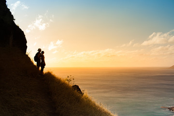 Man and woman hikers standing on edge of mountain watching the sunset