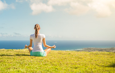 Young female meditating on grass field