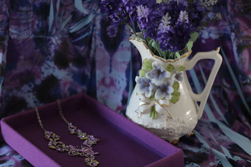 white porcelain pitcher with purple flowers next to a purple box with a pretty necklace with a floral purple background
