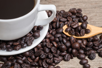 Coffee cup and coffee beans with wood spoon on Plank