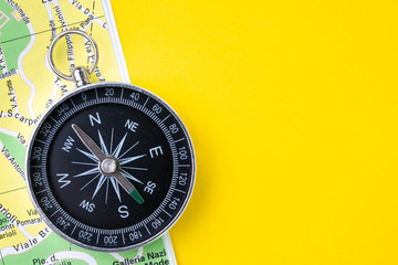 Compass on paper map with street for travel or driving navigation on vivid yellow background with copy space using for road trip on holiday or start new adventure or wanderlust life journey