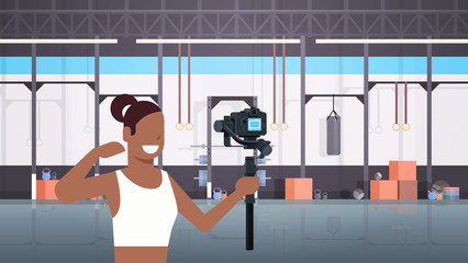 woman fitness blogger shooting selfie video african american girl in front of camera recording herself using gimbal stabilizer blogging concept modern gym interior horizontal