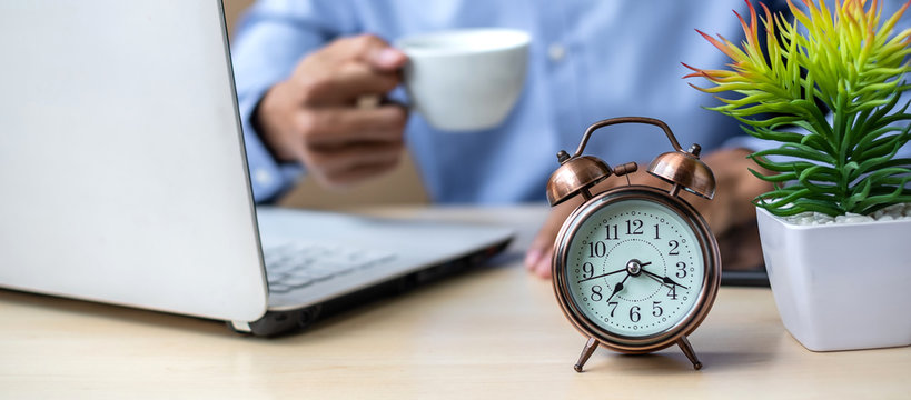 Close up alarm clock with young Businessman using laptop analysis marketing plan and drinking coffee in the morning. Business, Finance and lifestyle concepts