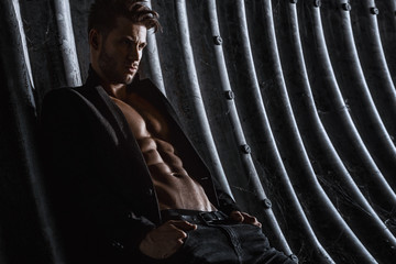 Muscular young man with beard on dark tunnel urban background. Fashion portrait of brutal strong muscle guy with modern trendy hairstyle. Model, fashion concept. Sexy naked torso, six pack abs. Wall mural