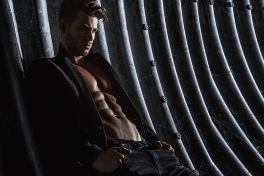 Muscular young man with beard on dark tunnel urban background. Fashion portrait of brutal strong muscle guy with modern trendy hairstyle. Model, fashion concept. Sexy naked torso, six pack abs.