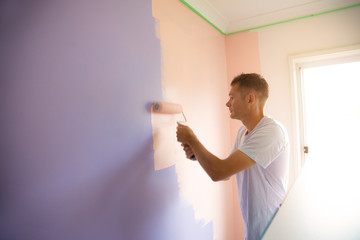 Young man painting an internal wall