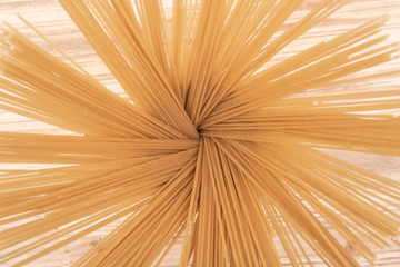 Abstract image from above of an Organic uncooked Brown Rice Spaghetti pasta arranged in a ceramic tall jar. Gluten-free and sodium-free  alternative to traditional pastas.