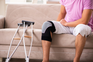 Young man with injured knee recovering at home
