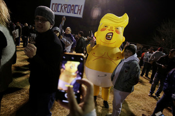 A man wearing an inflatable suit representing U.S. President Donald Trump poses for a photo with a child during the 'March for Truth: Stop the Wall, Stop the Lies' during the visit of U.S. President Trump to El Paso