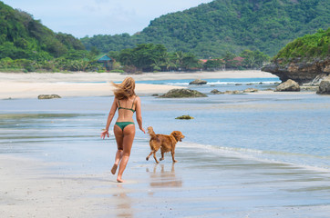 Anonymous girl bouncing and playing with a golden retriever on a white sand beach. Human's best friend.