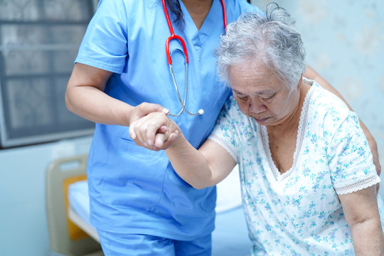 Asian nurse physiotherapist doctor care, help and support senior or elderly old lady woman patient get up from bed at hospital ward : healthy strong medical concept.