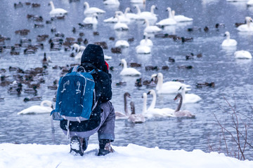 A photographer is take photos besides a lake in snow shower