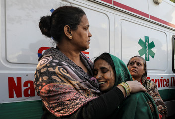 A woman cries as she cannot find her relative who was staying in a hotel where a fire broke out in New Delhi