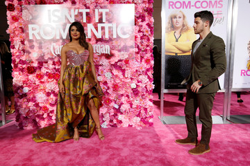 "Cast member Chopra poses as husband Jonas watches at the premiere for the movie ""Isn't It Romantic"" in Los Angeles"