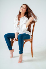 Beauty fashion portrait of smiling sensual asian young woman with dark long hair in white shirt sitting on chair on white background