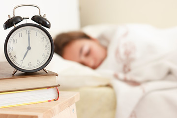 Teenager girl sleeping in a white bed. Alarm clock in the foreground on a pile of books