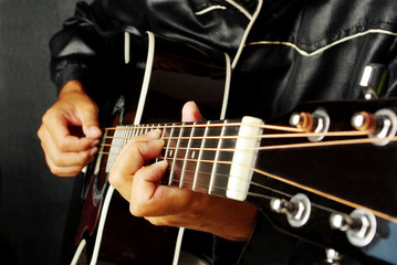 Guitarist plays the guitar. Close-up.