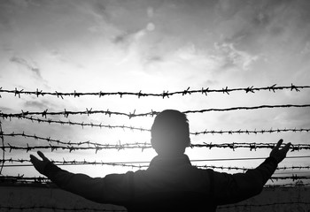 social justice abstract concept: with blurry barbed wire rod fence