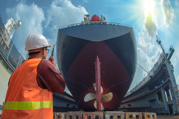 Obraz supervisor, foreman, inspector, surveyor takes final inspection of the cleaning, repairing, recondition of over hull of the commercial ship in dry dock yard, ready to delivery the ship to the sea - fototapety do salonu