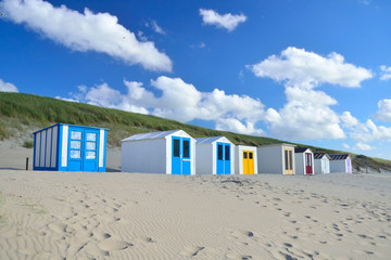 Row of colorful wooden beach sheds on the beach of island Texel in the Netherlands