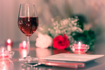 Wall Mural - glass of red wine and roses on restaurant table