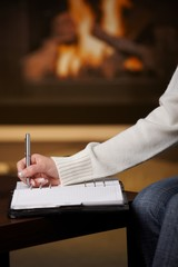 Hand writing in notepad in front of fireplace