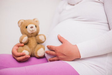 Close up of pregnant woman holding teddy bear.