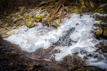 Small stream and waterfall in winter with ice