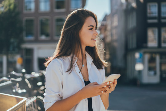 Pretty smiling happy girl holding mobile phone in her hands and browsing internet while waiting to her friend standing on the street, typing in messenger and scrolling web pages