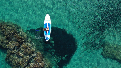 Aerial drone bird's eye view of 2 men exercising sup board in turquoise tropical clear waters Wall mural