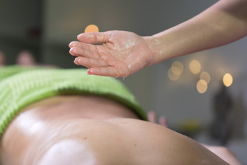Hand pouring oil for massage in spa studio. Massage oil drop