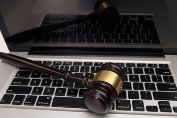 Wooden gavel on laptop keyboard. auction, online, law, technology, justice concept