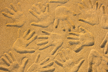 hand prints on yellow sand close up. natural surface texture
