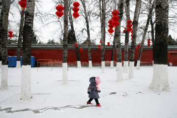A girl draws a track into the snow in Ditan Park in Beijing