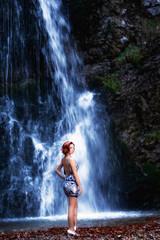 Rothaarige Frau vor einem Wasserfall