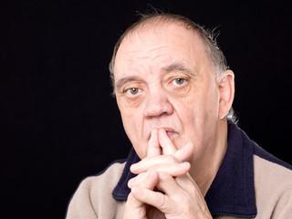Homme âgé réfléchissant de face isolé sur fond noir