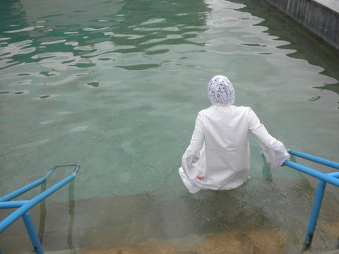 Young woman during traditional baptism ceremony,empty space