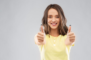 gesture and people concept - smiling young woman or teenage girl in blank yellow t-shirt showing thumbs up over grey background