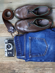 Still life with blue jeans, brown boots, leather belt and camera